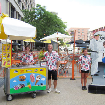 Event staff poses next to ice cream carts during a Hawaiian Luau themed outdoor event.